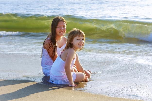 Bonitos meninas brincando na praia juntos durante as férias de verão