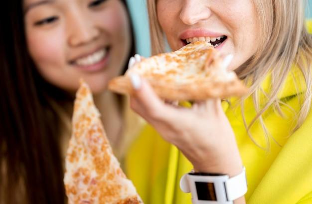Bonitos mulheres asiáticas comendo pizza