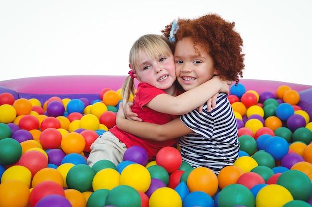 Bonitos sorridentes meninas na piscina de bola de esponja abraçando