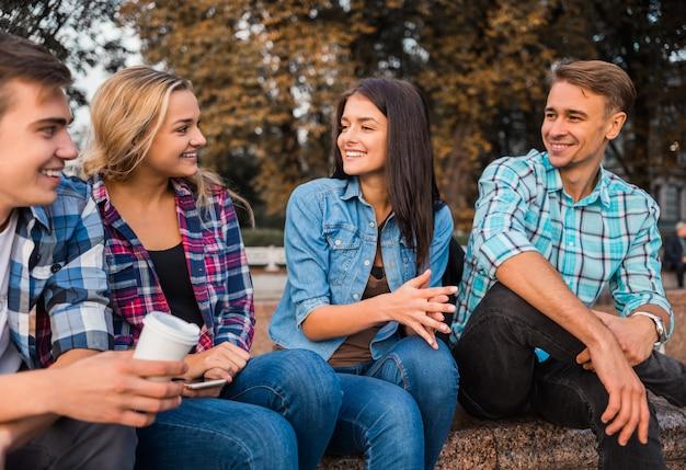 Bons alunos sentam no banco e sorriem juntos.