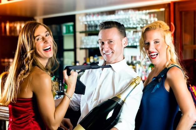 Bons amigos, barman e mulheres - com uma grande garrafa de champanhe magnum no bar se divertindo, ela puxa a gravata dele