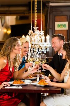 Bons amigos para jantar ou almoçar em um restaurante fino, tilintar de copos