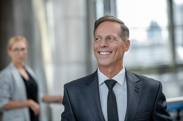Bons momentos. homem adulto determinado com sorriso dentuço em terno escuro formal e gravata esperando no aeroporto e a mulher atrás