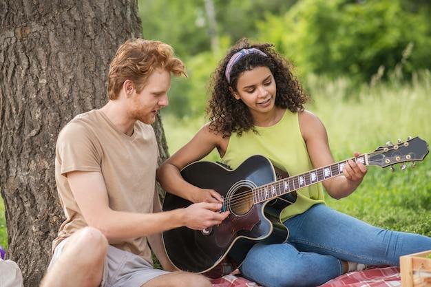 Bons momentos. jovem carinhoso e linda garota sorridente com um violão passando o lazer de verão no parque em xadrez
