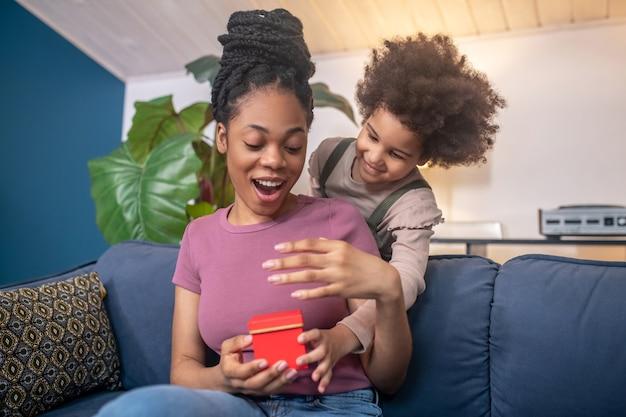 Bons momentos. mulher afro-americana jovem adulta entusiasmada e uma linda filha com um presente numa caixa vermelha atrás do sofá em casa