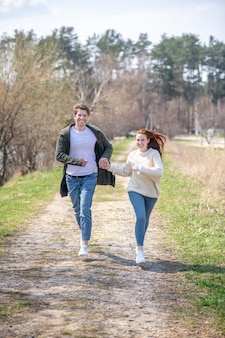 Bons momentos. sorrindo, homem e mulher enérgicos de suéter e jeans correndo ativamente, passando tempo de lazer na natureza em um dia ensolarado de primavera