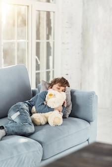 Bons sonhos. adorável garotinho louro abraçando seu lindo brinquedo favorito e deitado no sofá enquanto tira uma soneca