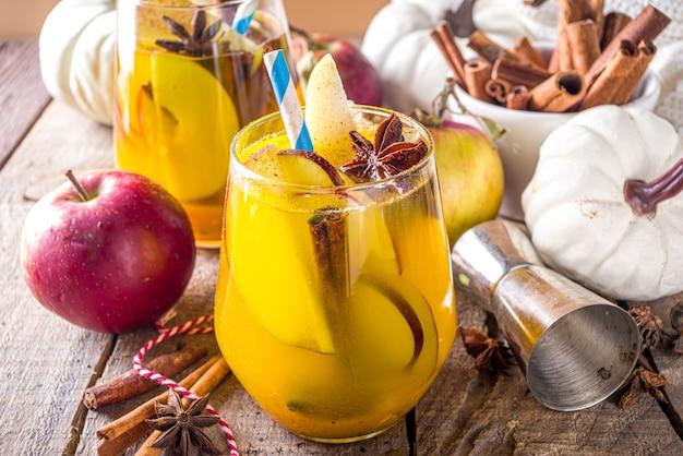 Boozy pumpkin party punch, sangria de ação de graças com suco de abóbora, maçã, pêra e especiarias, fundo de madeira aconchegante com suéter quente e espaço de cópia de ingredientes