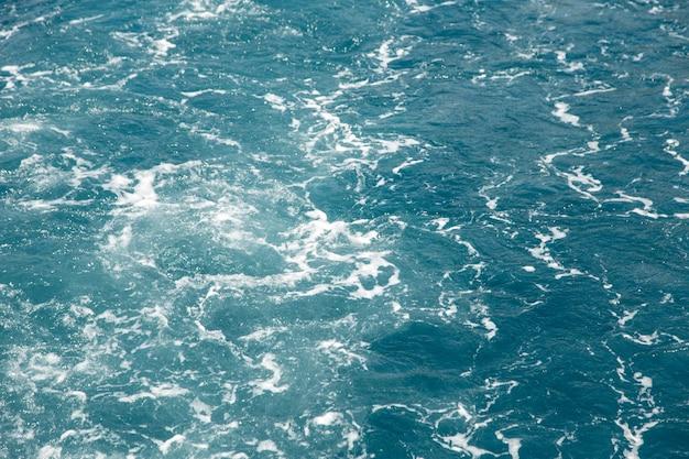 Borbulhando água e espuma do mar do motor do barco, o conceito de movimento da água, cor do mar de cascalho.