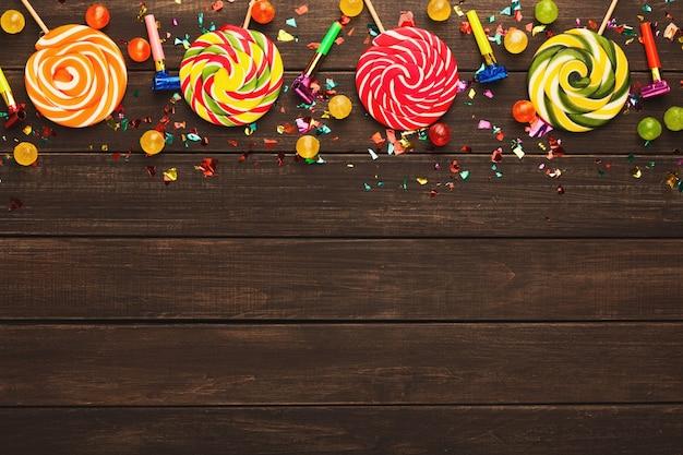 Borda colorida de pirulitos espirais em fundo de madeira