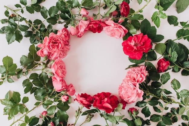 Borda da moldura da coroa redonda feita de flores e folhas de rosas vermelhas e rosa