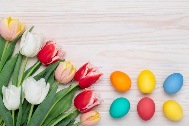 Borda da moldura de páscoa feliz, ovos pascais em uma parede de madeira branca