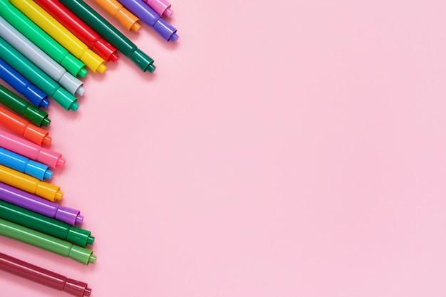 Borda de canetas de ponta de feltro coloridas no fundo rosa com copyspace