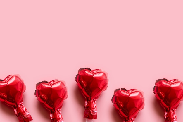 Borda de corações de balões de folha vermelha em fundo rosa