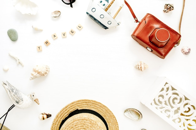 Borda de moldura redonda com espaço de cópia da composição de viagem com chapéu de palha, câmera retro, escultura de pássaro, barco de brinquedo, conchas na superfície branca