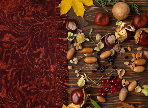 Borda de outono vintage e folhas caídas na velha mesa de madeira, vista superior