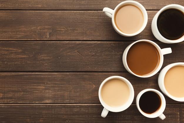 Borda de vários tipos de café em xícaras de tamanhos diferentes em uma mesa de madeira rústica, vista de cima, espaço de cópia