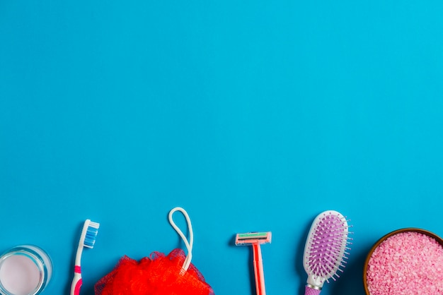 Borda inferior feita com escova de cabelo; creme; escova dental; navalha; sopro de banho e sal em pano de fundo azul