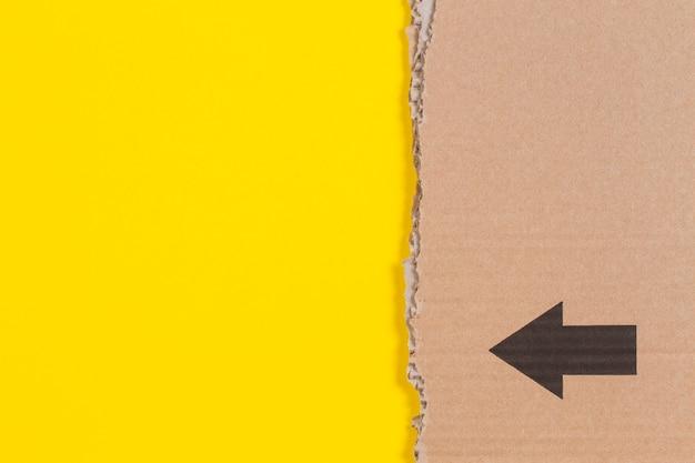 Borda irregular de papelão ondulado marrom com seta preta na parede amarela