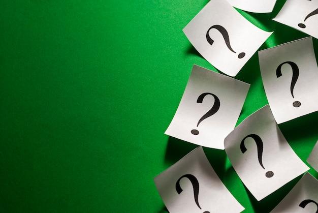 Borda lateral de pontos de interrogação dispersos em pequenos cartões brancos