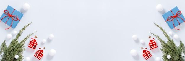 Borda mínima de natal branca e vermelha com galho de árvore de natal, decoração em vermelho, caixas e cones azuis para presente, configuração plana, espaço de cópia, banner da web