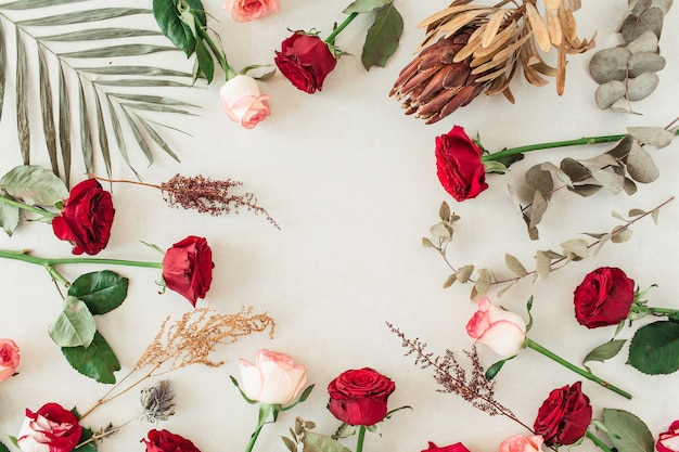 Borda plana do quadro com cópia em branco de maquete feita de flores rosas vermelhas e rosa, protea, folha de palmeira tropical, eucalipto em bege