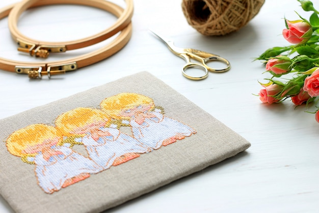 Bordado, aro, tesoura, flores no conceito de bordado de fundo branco de madeira