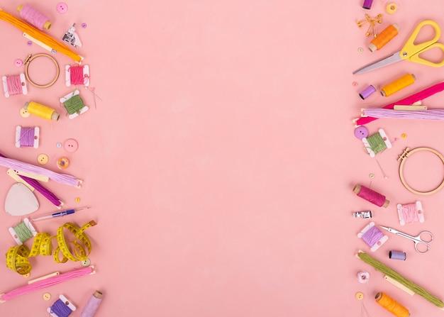 Bordado e ponto cruz de acessórios em fundo rosa. lay plana. copie o espaço.