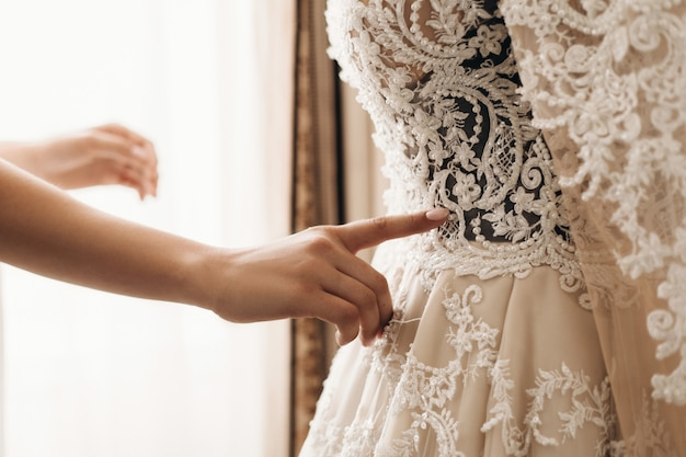 Bordado no lindo vestido de noiva, preparando-se para a cerimônia de casamento, vestido artesanal de alta costura