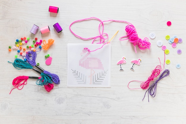 Bordado rosa com elementos decorativos em plano de fundo texturizado de madeira