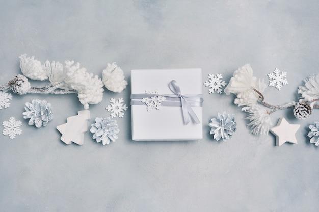 Border design um cartão de natal com caixa de presente de natal, cones, flocos de neve