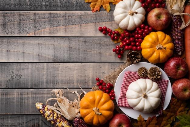 Bordo de outono parte com abóbora, milho e bagas vermelhas