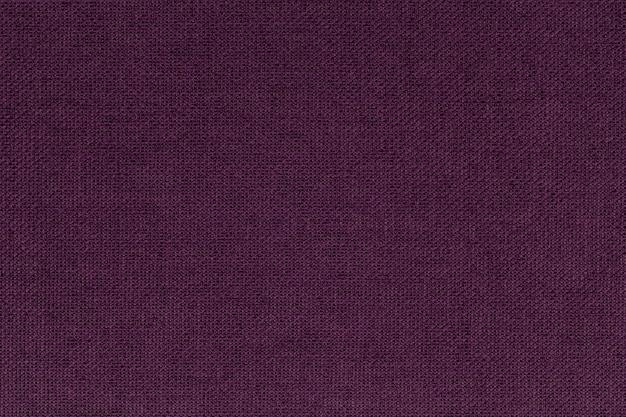 Borgonha escura, roxa de um material têxtil. tecido com textura natural. pano de fundo.