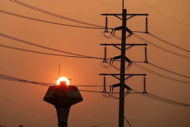 Borne de alta tensão ao pôr do sol