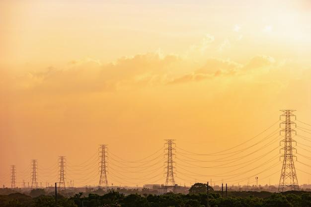 Borne de alta tensão, torre de alta tensão com o céu no fundo do por do sol.