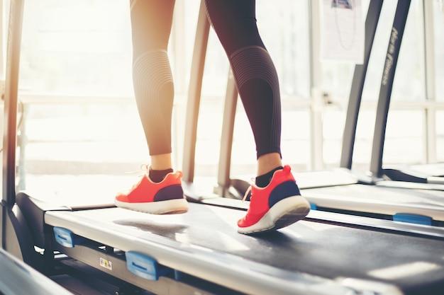 Borradas de execução de sapatas do esporte na academia, enquanto uma jovem está tendo jogging