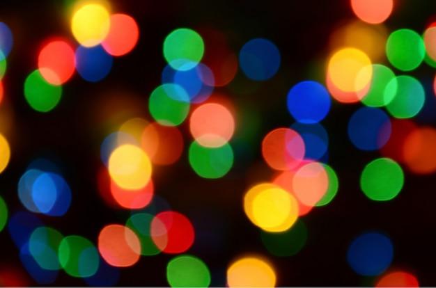 Borradas festivas luzes coloridas sobre preto útil como plano de fundo