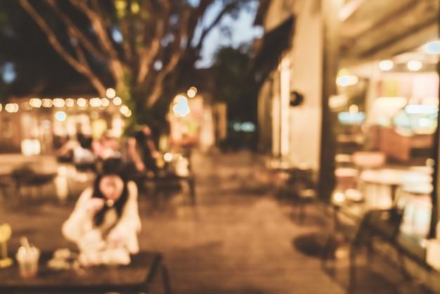 Borrão abstrato pátio para convívio ao ar livre em café restaurante à noite