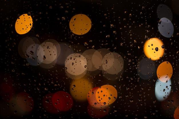 Borrão de luz através do vidro da chuva.