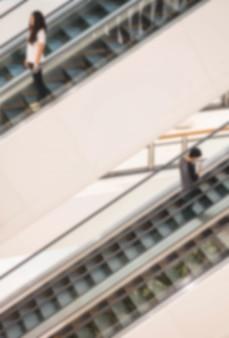 Borrão de movimento da escada rolante em loja de departamento