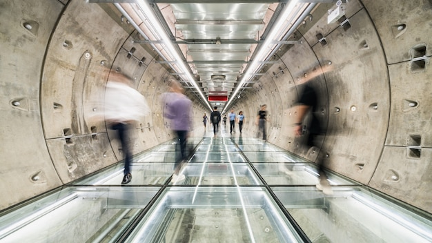 Borrão de movimento de pessoas asiáticas andando na passagem do túnel do metrô