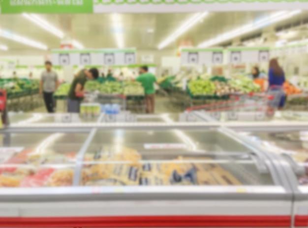 Borrão de movimento de prateleiras de frutas à venda no supermercado com algumas pessoas compras