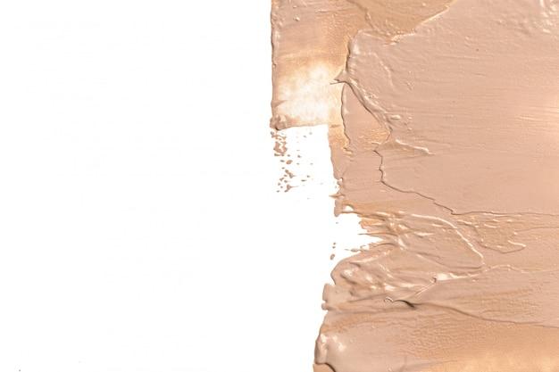 Borrão líquido da fundação no fundo branco.