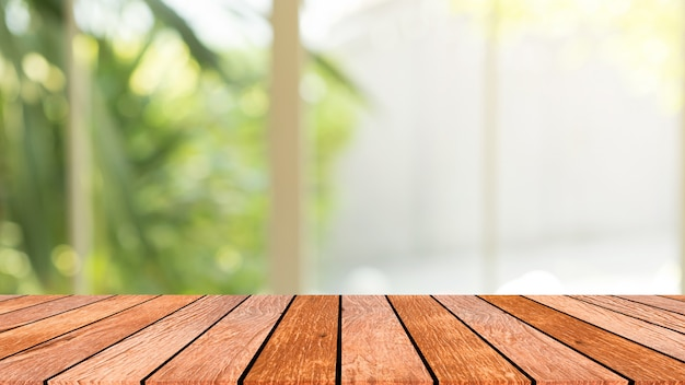 Borrão vista para o jardim da janela com a luz da manhã com perspectiva de mesa de madeira para o fundo