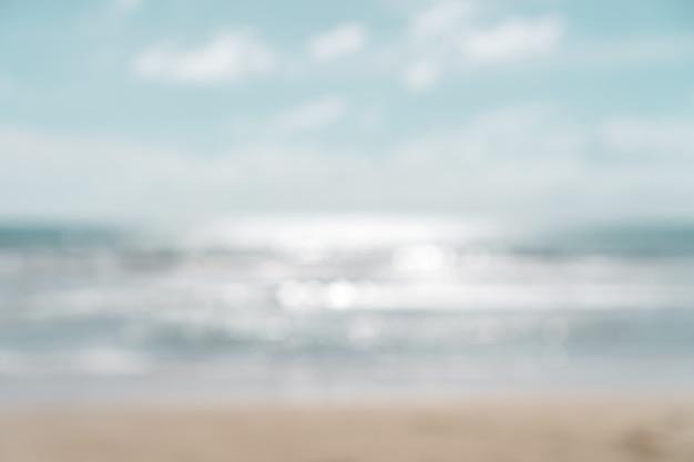 Borre a praia do bokeh do verão com luz do sol e o céu azul.