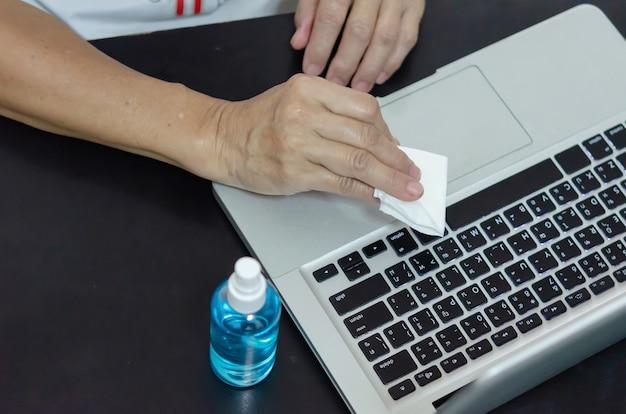 Borrifar álcool para limpar o computador e eliminar os germes. conceito de cuidados de saúde.