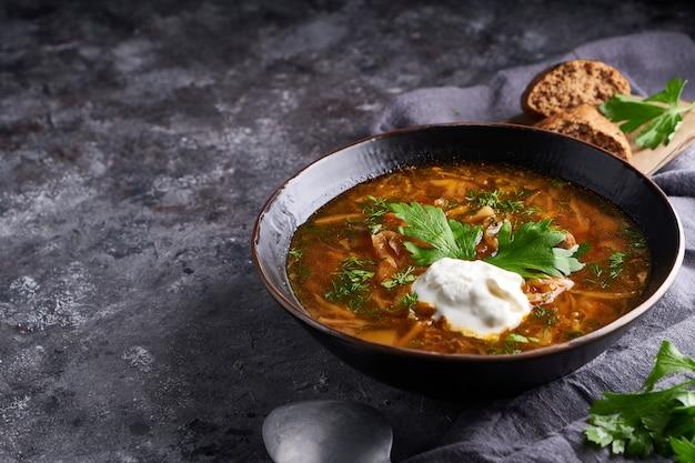 Borsch de sopa tradicional da europa e da rússia com repolho, creme de leite e carne, servido em um prato sobre uma mesa de pedra escura