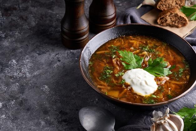 Borsch de sopa tradicional europeia e russa com couve, creme de leite e carne, servido em um prato sobre uma mesa de pedra escura