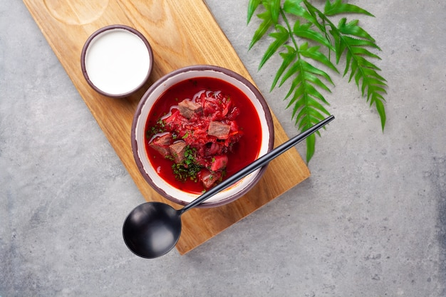 Borsch tradicional ucraniana e russa, sopa vermelha com beterraba, carne, creme de leite, colher na placa de madeira na mesa cinza, close-up, topo
