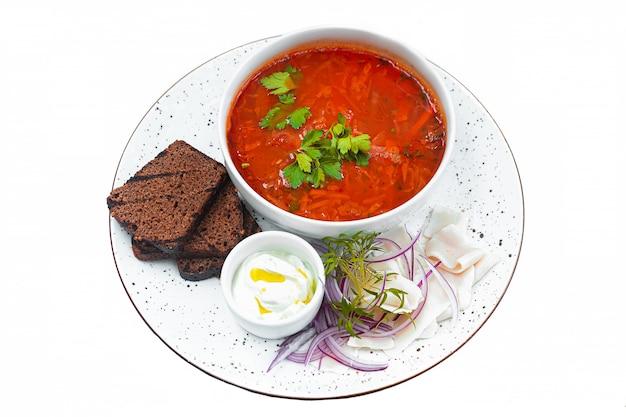 Borsch vermelho ucraniano, cozinha tradicional, receitas deliciosas. fatias de pão preto, pão torrado com alho, cebola crua picada e banha em um prato branco isolado em um fundo branco.